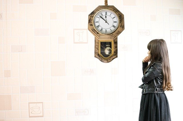時計を気にする子どもの画像